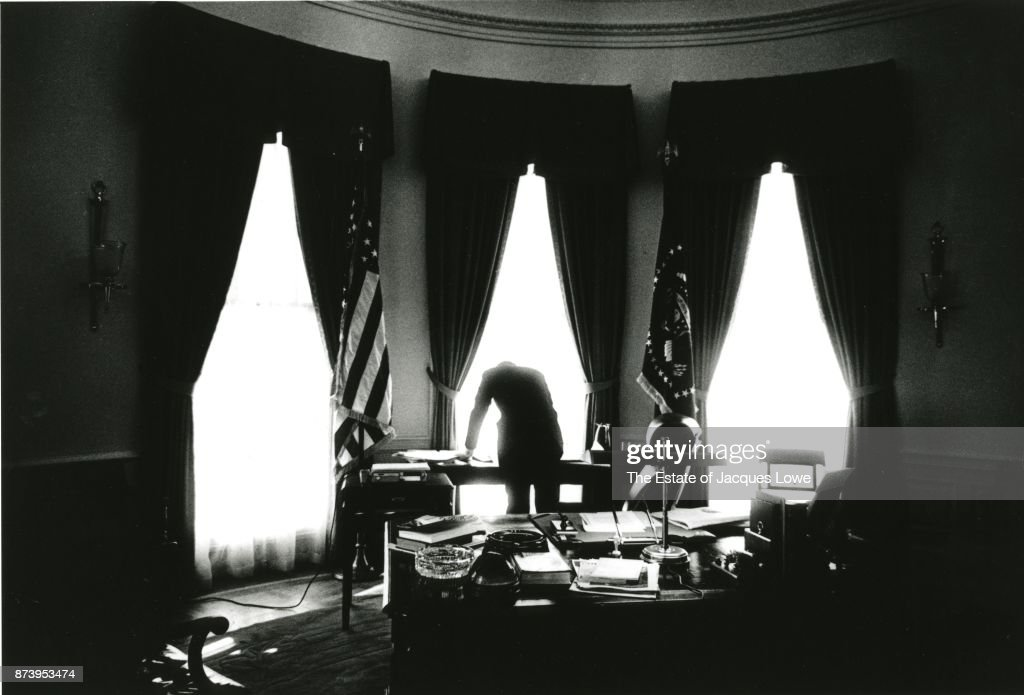 View, from behind, of US President John F Kennedy (1917 - 1963) as he leans over a desk in the Oval Office, Washington DC, 1961.