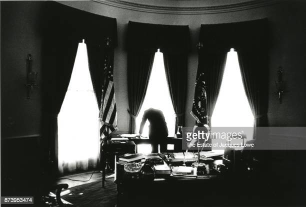 View from behind of US President John F Kennedy as he leans over a desk in the Oval Office Washington DC 1961