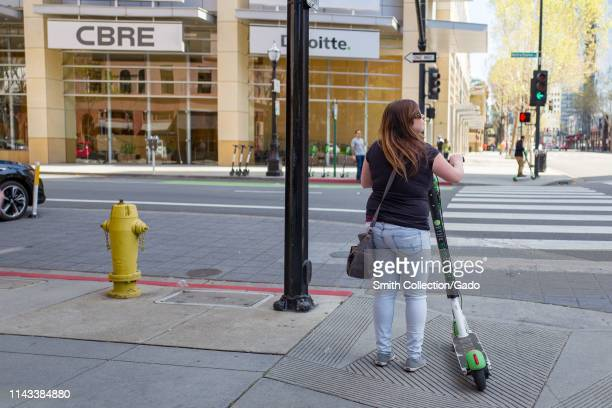 View from behind of woman holding a Lime micromobility scooter and preparing to cross intersection in the Silicon Valley town of San Jose California...