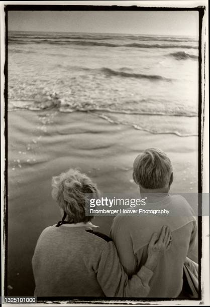 View, from behind, on an unidentified as they sit together a look out to the Pacific Ocean, Half Moon Bay, California, 1993.