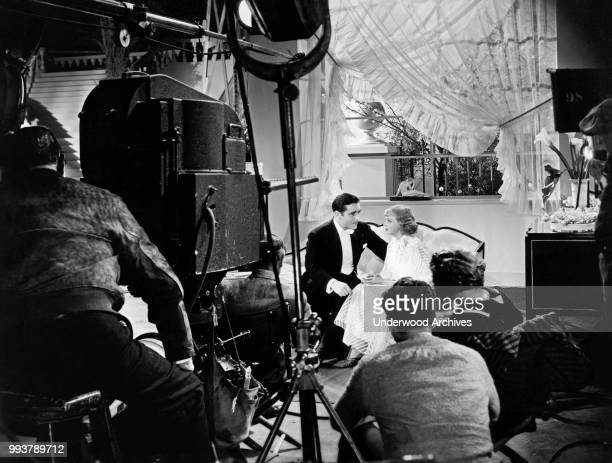 View from behind the camera operator of American film director Norman Z McLeod as he watches actors John Boles and Dixie Lee in a scene from the...
