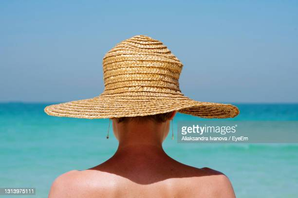 view from behind woman at the beach wearing straw hat against the sea - 麦わら ストックフォトと画像