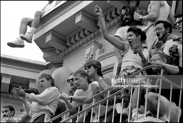 View, from below, of people as they watch and cheer from a balcony on Market Street during the International Lesbian & Gay Freedom Day Parade, San...