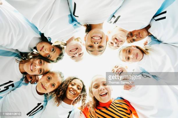view from below of smiling young female soccer players in huddle before game - football team stock pictures, royalty-free photos & images