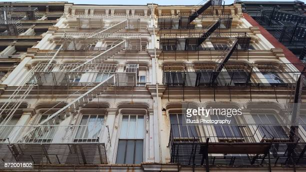 view from below of typical cast iron buildings with fire escapes along greene street in soho, new york city - soho new york stock pictures, royalty-free photos & images