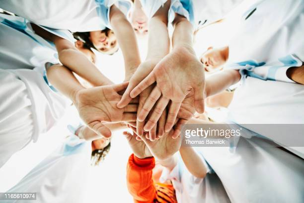 view from below of young female soccer players bringing hands together before game - teamwerk stockfoto's en -beelden