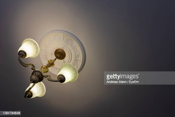view from below on a retro style ornate metal chandelier with three lamps hanging from a ceiling. - household fixture stock pictures, royalty-free photos & images