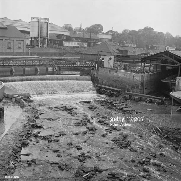 View from Brentford of the River Brent with Johnsons Island boatyard on the right, a weir in the centre and Brentford Dock in the background, at...