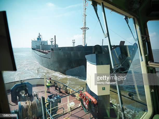 View from bridge of tugboat of sailor tyring tow lines to ship at sea