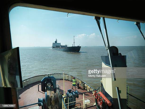 View from bridge of tugboat of ship approaching at sea