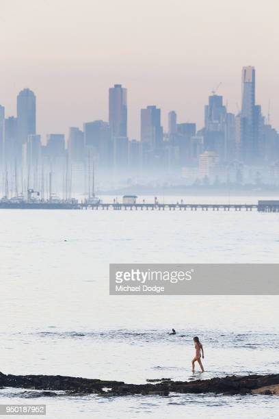 A view from Brighton foreshore is seen as as a beach goer walk into the water during the evening of April 23 2018 in Melbourne Australia Melbourne...