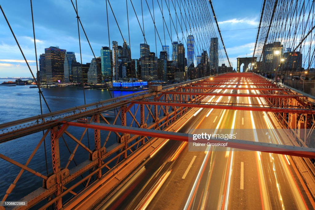 View from Brooklyn Bridge at the Skyline of Downtown Manhattan with light trails of the traffic on the bridge : Stock-Foto