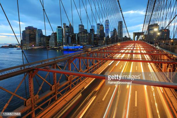 view from brooklyn bridge at the skyline of downtown manhattan with light trails of the traffic on the bridge - rainer grosskopf stock pictures, royalty-free photos & images