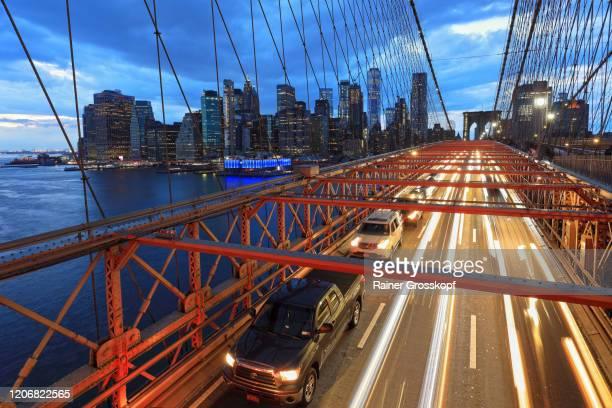 view from brooklyn bridge at the skyline of downtown manhattan with light trails of the traffic on the bridge - rainer grosskopf stock-fotos und bilder