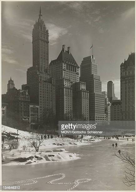 View from Central Park over the pond towards 5th Avenue at 59th Street. Snow is on the ground, the pond is frozen and people are walking on the ice....