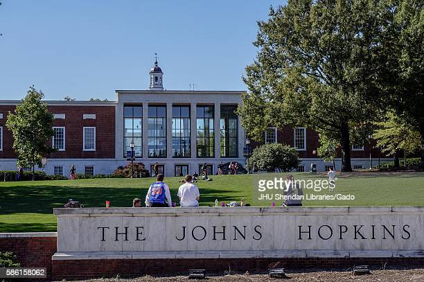 A view from Charles street of the grassy Beach and Milton S Eisenhower Library of the Johns Hopkins University three male students their backs facing...