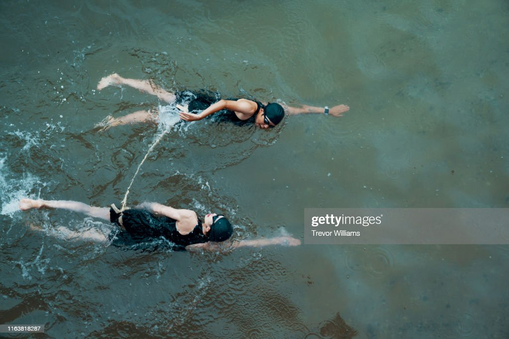 View from directly above a visually impaired female triathlete swimming in the ocean with her guide : ストックフォト