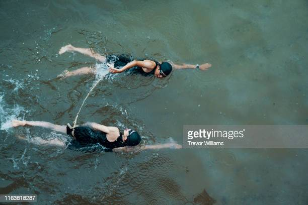View from directly above a visually impaired female triathlete swimming in the ocean with her guide