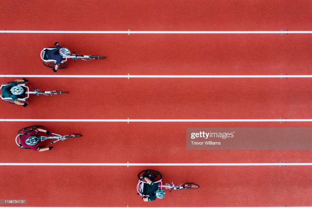 View from directly above four women racing in wheelchairs : Photo