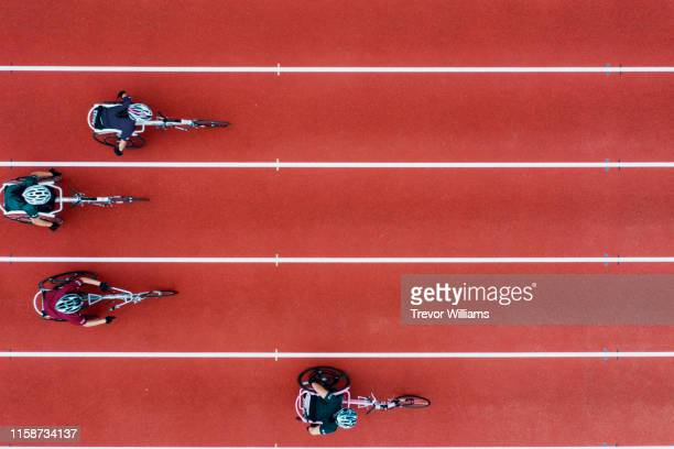 view from directly above four women racing in wheelchairs - athleticism stock pictures, royalty-free photos & images