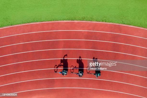 view from directly above three men wheelchair racing on a track. - baanevenement mannen stockfoto's en -beelden