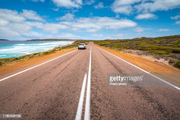 view from empty country road sightseeing scenic landscape view of great ocean road in victoria, australia. bright sunny summer day with warm light and blue sky with cloud and surfing wave. famous drive route in australia. - western australia stock-fotos und bilder