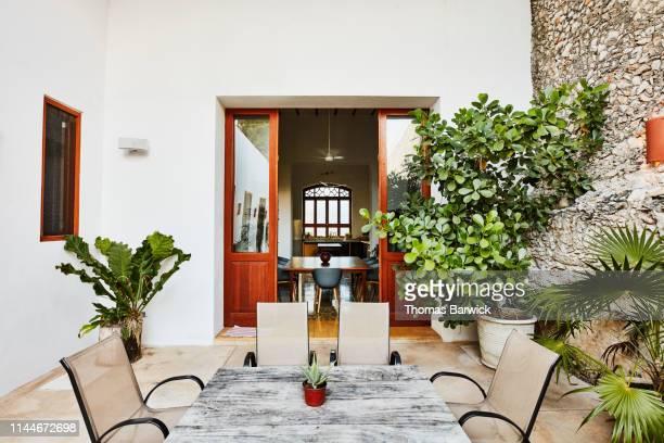 view from exterior courtyard into dining room of home - courtyard - fotografias e filmes do acervo