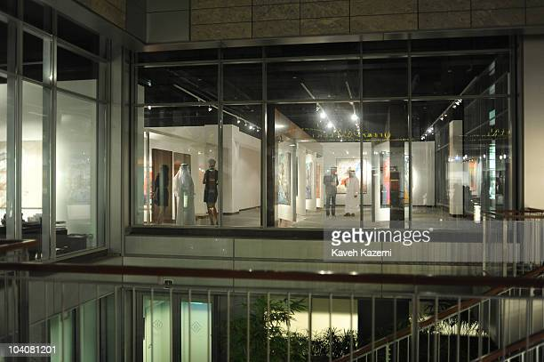 View from exteriors of a modern gallery with Emirati men wearing their traditional costumes during an arts evening held at galleries and public...