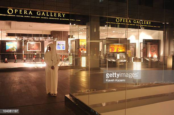 View from exteriors of Opera gallery with an Emirati man wearing traditional costume standing outside during an arts evening held at galleries and...