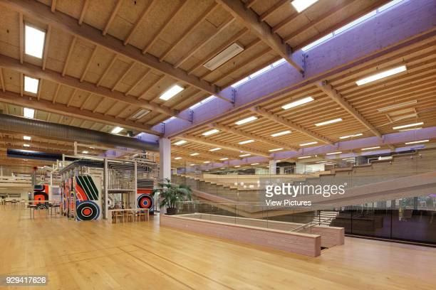 View from ground floor to timber amphitheatre with paint bottling tanks in background IBC Innovation Factory Kolding Denmark Architect schmidt hammer...