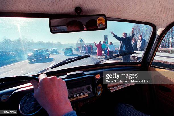 View from inside a car of West Germans as they stand by the side of the road and wave welcoming East Germans across the newly opened border between...