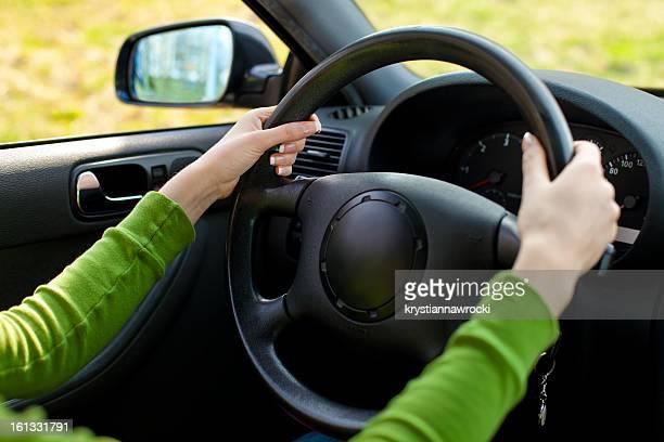 Vista da interno auto a donna le mani sul volante