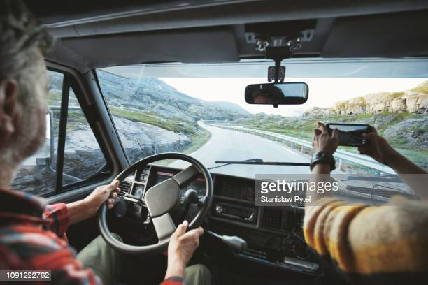 view from inside of campervan when traveling on beautiful road - camper stockfoto's en -beelden