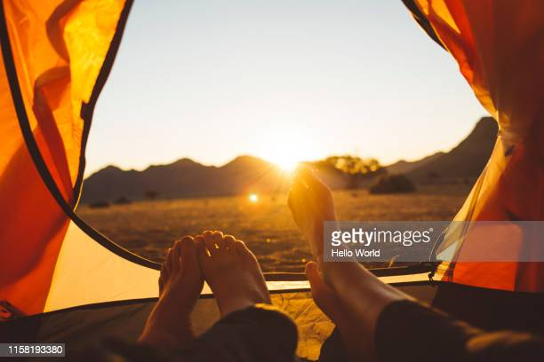 view from inside tent of feet and sun setting - spirituality stock pictures, royalty-free photos & images