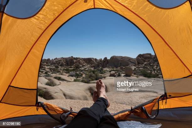 view from inside tent with mans feet out - joshua tree stock photos and pictures