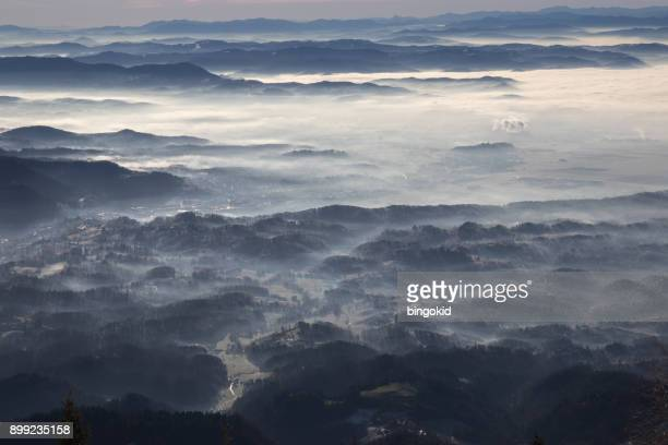 view from mountain top to fog down in the valley - kranj stock pictures, royalty-free photos & images