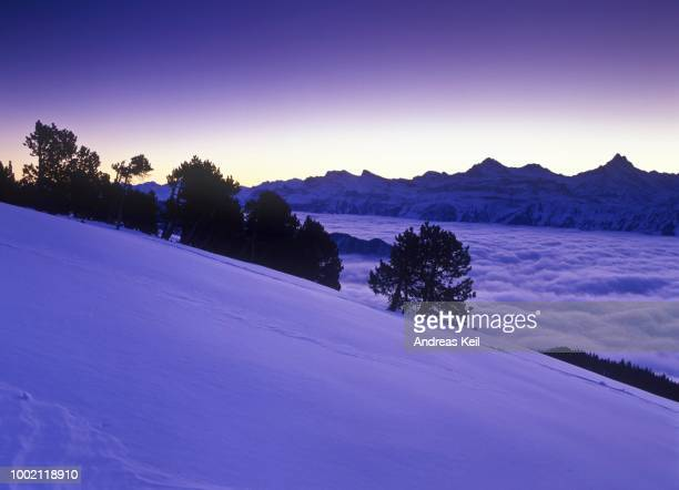 View from Niederhorn Mountain towards 4000m high mountains in winter before sunrise, fog filled valley, Bern, Switzerland