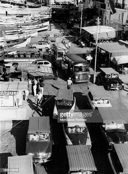 A view from on high of Marina Piccola pier full of taxis and buses in the background some boats docked at the quay Capri Italy 1962