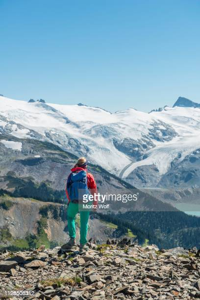 view from panorama ridge, hiker in front of a mountain range with glacier, guard mountain and deception peak, garibaldi provincial park, british columbia, canada - garibaldi park stock pictures, royalty-free photos & images
