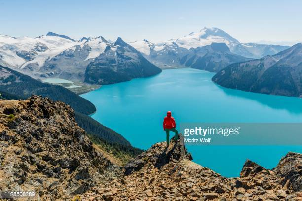 view from panorama ridge hiking trail, hiker on a rock, garibaldi lake, guard mountain and deception peak, back glacier, garibaldi provincial park, british columbia, canada - garibaldi park stock pictures, royalty-free photos & images