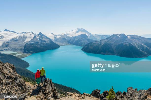 view from panorama ridge trail, two hikers on a rock, garibaldi lake, turquoise glacial lake, guard mountain and deception peak, rear glacier, garibaldi provincial park, british columbia, canada - garibaldi park stock pictures, royalty-free photos & images