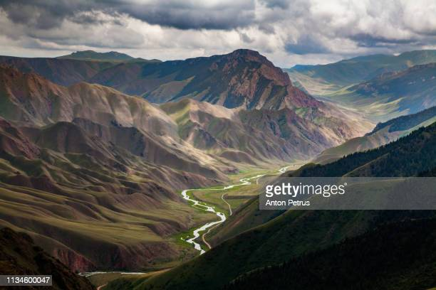 view from pass to green valley and the mountains. kyrgyzstan - kyrgyzstan stock pictures, royalty-free photos & images