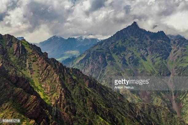 view from pass to green valley and the mountains. kyrgyzstan - flanco de valle fotografías e imágenes de stock