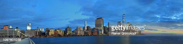 view from pier 34 in hudson river at the skyline of downtown manhattan with one world trade center at dusk - rainer grosskopf stock pictures, royalty-free photos & images