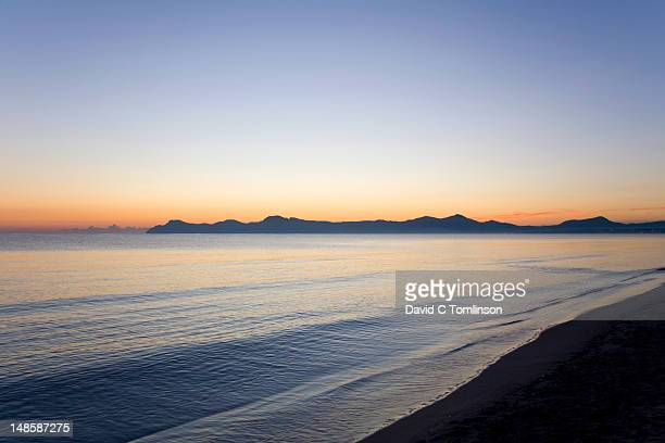 View from Platja de Muro across the calm waters of the Badia dÆAlcudia to the silhouetted peaks of the Parc Natural de la Peninsula de Llevant, at dawn.