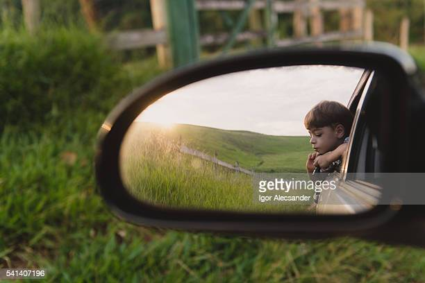 View from rearview mirror reflection of a young kid looking out the car window on a countryside area