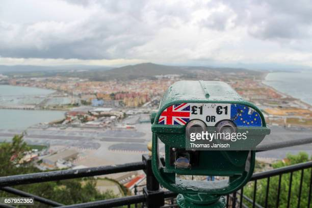view from rock of gibraltar towards spain with storm clouds and a telescope showing uk and the eu, gibraltar - brexit stock pictures, royalty-free photos & images