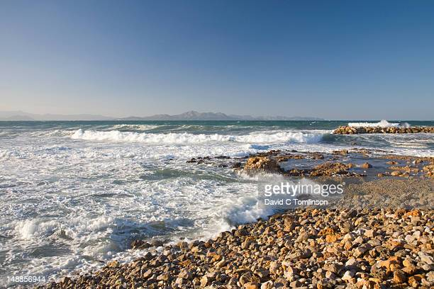 View from rocky shore with crashing surf across the Badia dÆAlcudia towards Cap des Pinar.