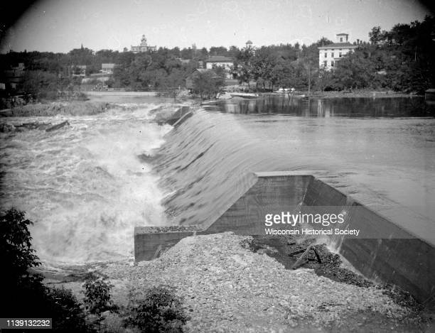View from shoreline looking across the dam in front Black River Falls Wisconsin 1911 Black River Falls is on the opposite shoreline with several...