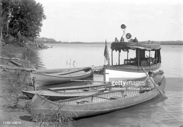 View from shoreline of small launch with two canoes and a rowboat on the shoreline of the Mississippi River Cassville Wisconsin 1910 There is a child...
